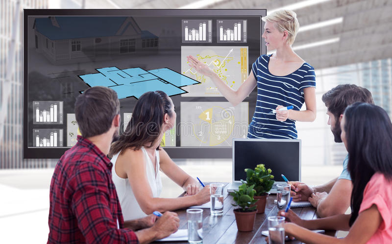 Composite image of casual businesswoman giving presentation to her colleagues stock photography