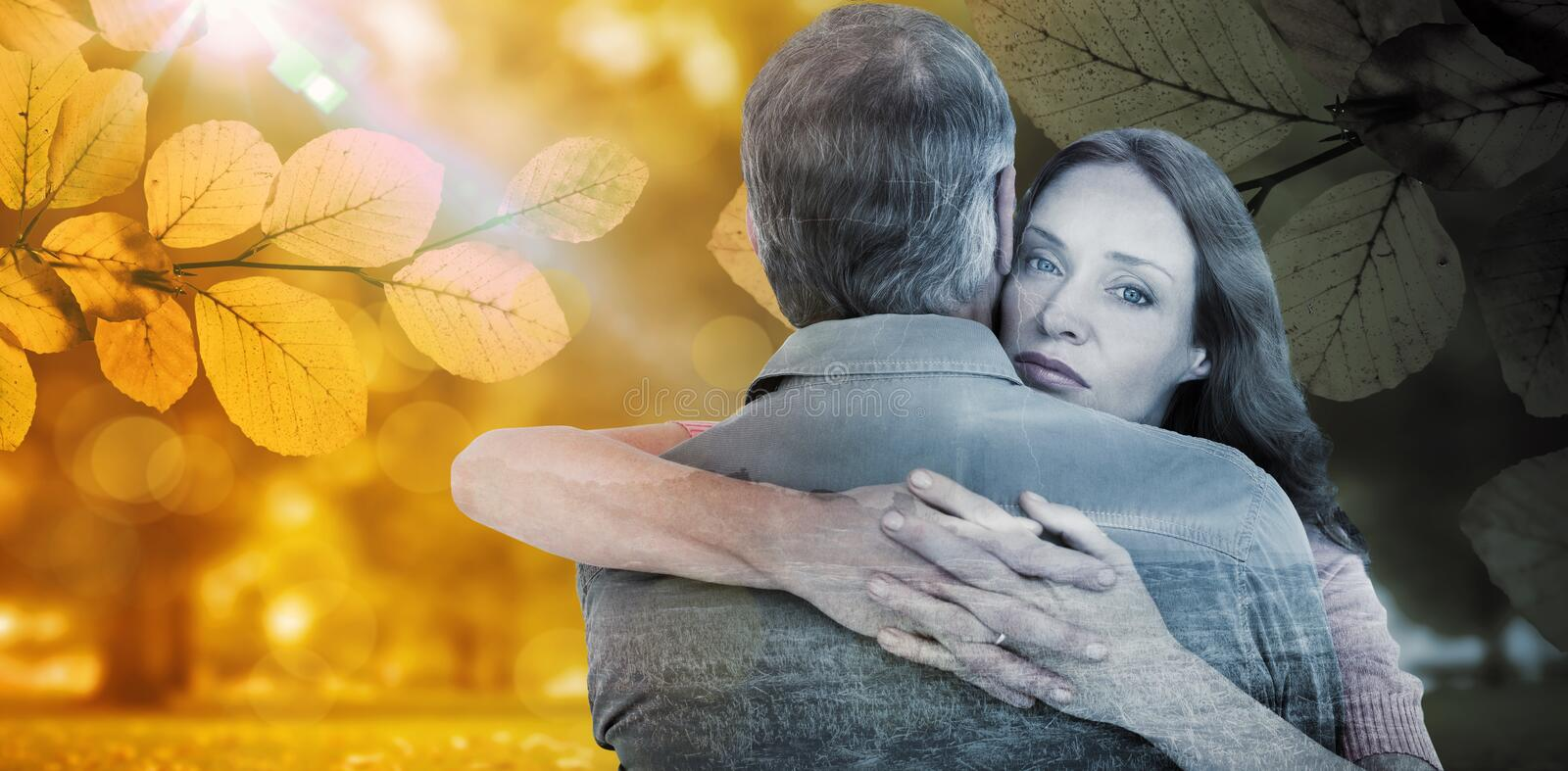 Composite image of casual couple hugging each other. Casual couple hugging each other against autumn scene royalty free stock photography