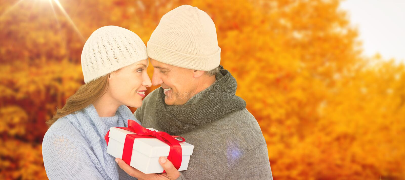 Composite image of casual couple in warm clothing holding gift. Casual couple in warm clothing holding gift against autumn scene stock photography