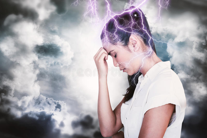 Composite image of casual upset businesswoman with head bowed. Casual upset businesswoman with head bowed against dark sky with white clouds royalty free stock photos