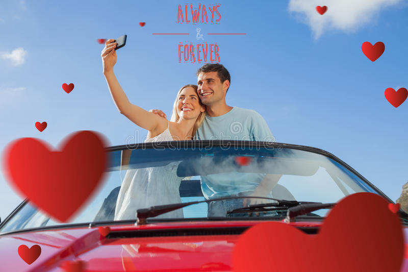 Composite image of cheerful couple standing in red cabriolet taking picture. Cheerful couple standing in red cabriolet taking picture against always and forever vector illustration