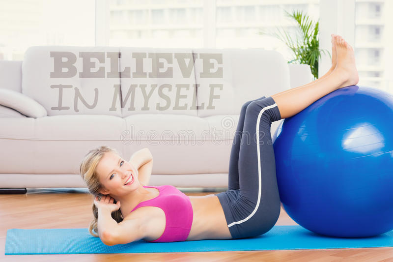 A Composite image of cheerful fit blonde doing sit ups with exercise ball royalty free stock images