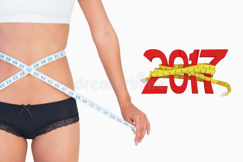 Composite image of cheerful slim woman measuring her waist stock images
