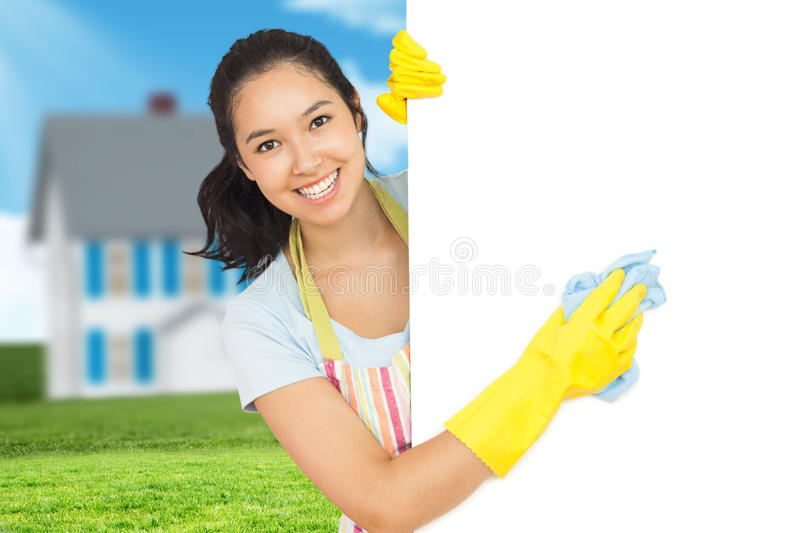 Composite image of cheerful woman cleaning white surface stock photography