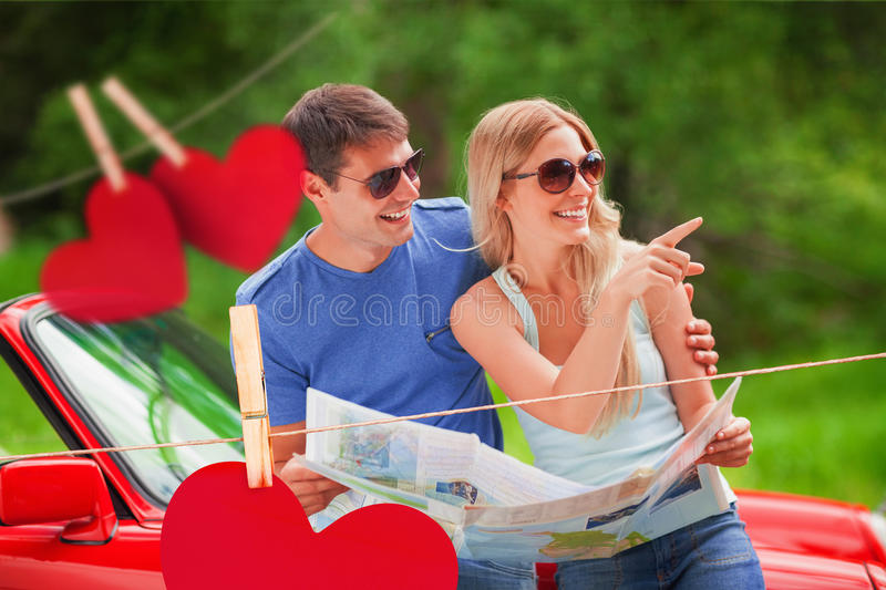 Composite image of cheerful young couple reading map. Cheerful young couple reading map against hearts hanging on a line stock illustration