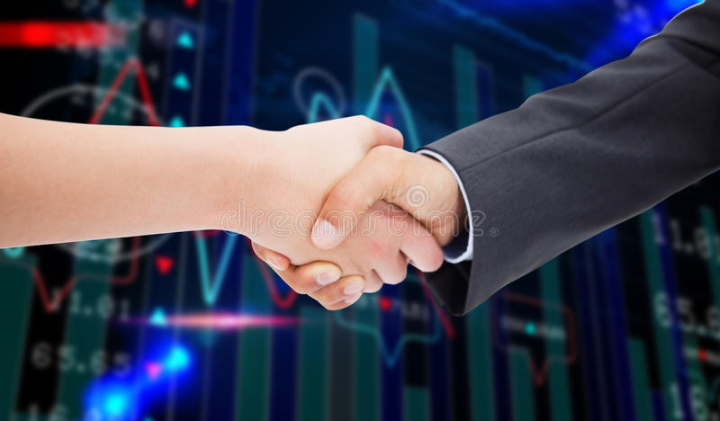 Composite image of close up of a handshake. Close up of a handshake against stocks and shares royalty free stock photo