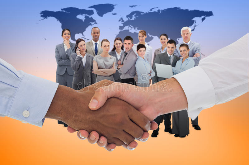 Composite image of close-up shot of a handshake in office. Close-up shot of a handshake in office against black world map stock images