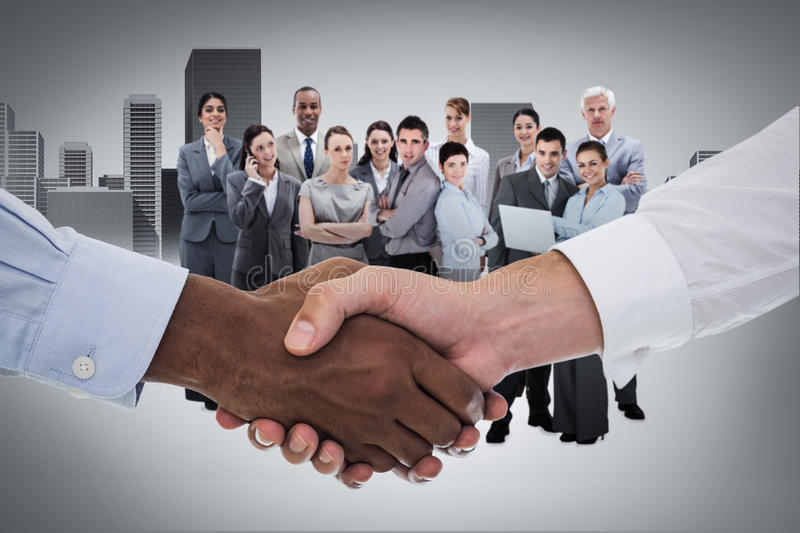 Composite image of close-up shot of a handshake in office. Close-up shot of a handshake in office against cityscape stock photography