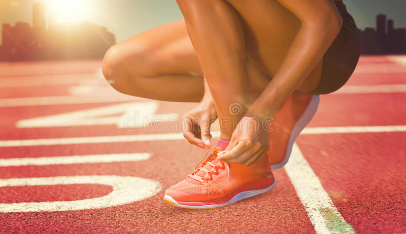 Composite image of close up of sportswoman is lacing shoes royalty free stock photos