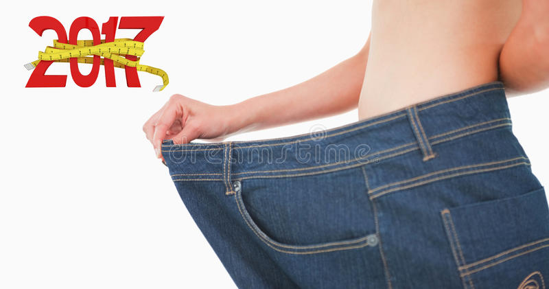 Composite image of close up of a woman belly in too big pants royalty free stock photo