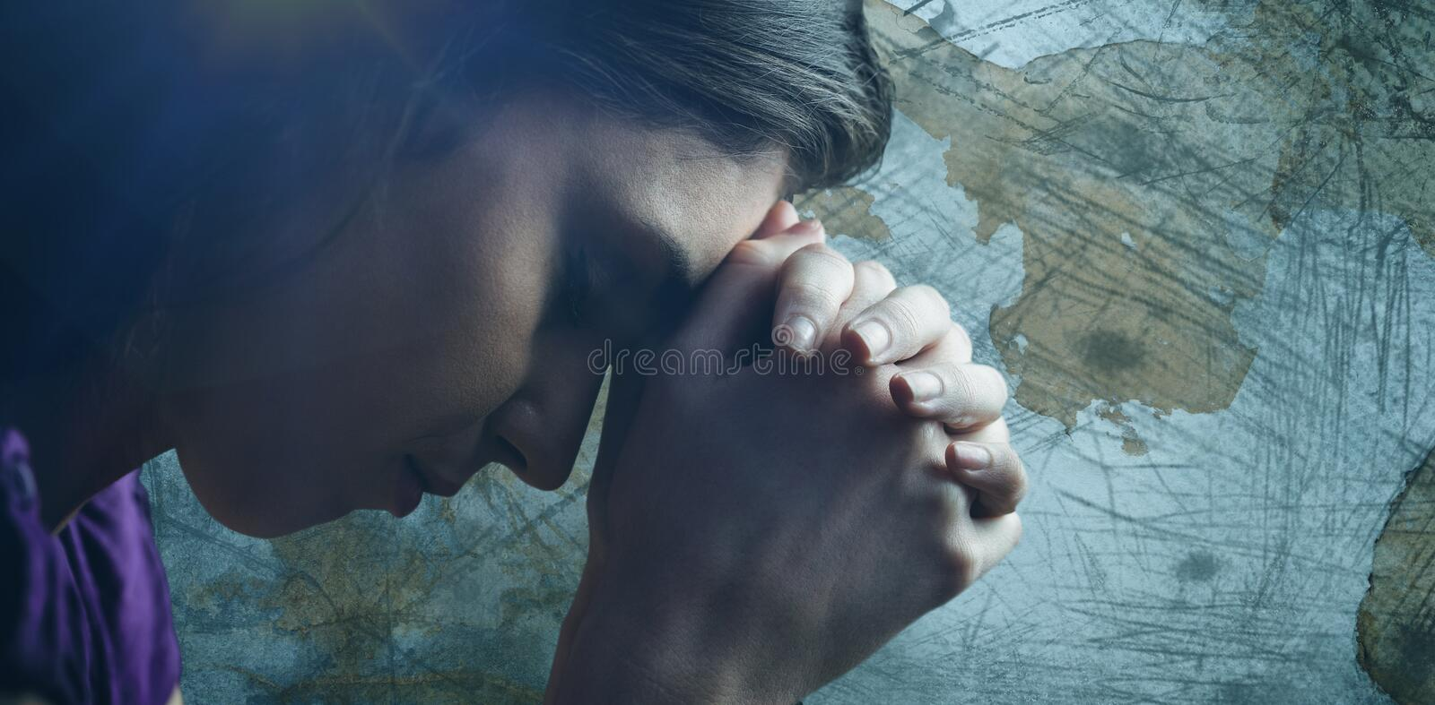 Composite image of close up of woman praying with hands together. Close up of woman praying with hands together against rusty weathered wall stock images