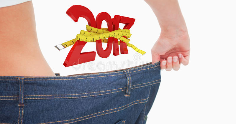 Composite image of close up of a woman waist in a too big pants. Close up of a woman waist in a too big pants against digital image of new year with tape measure stock images