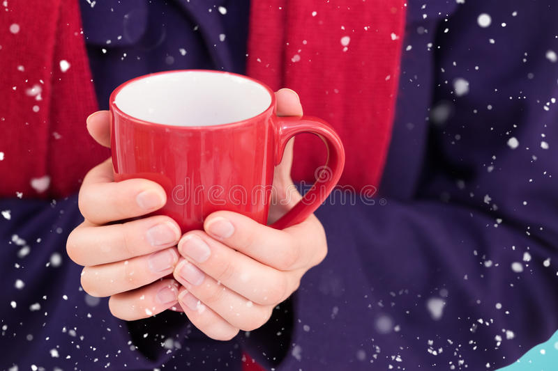 Composite image of close up of a woman in warm clothing holding mug. Close up of a woman in warm clothing holding mug against blue vignette royalty free stock photos