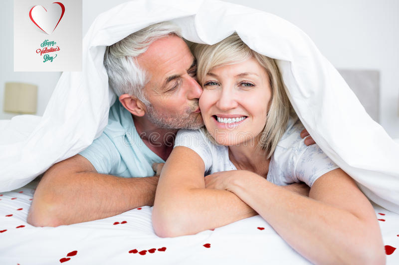 Composite image of closeup of mature man kissing womans cheek in bed. Closeup of mature men kissing womans cheek in bed against cute valentines message royalty free illustration