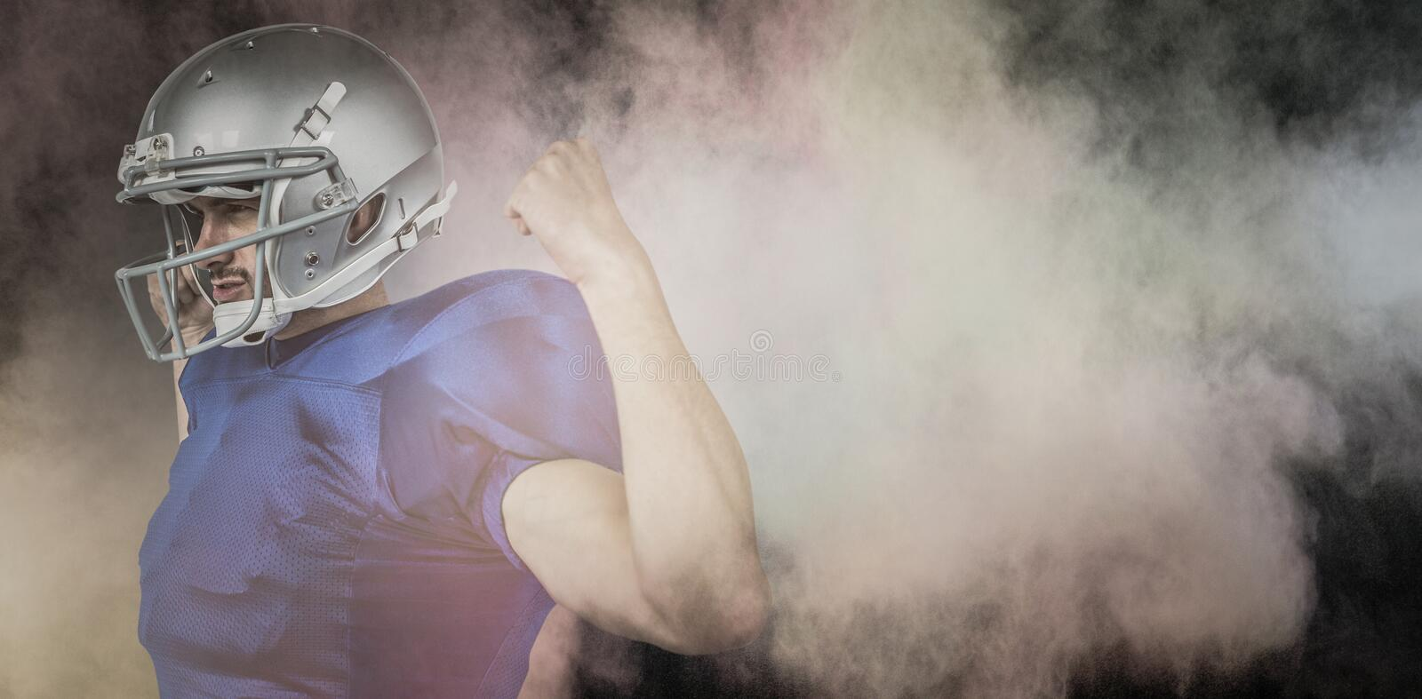 Composite image of confident american football player flexing muscles stock photo