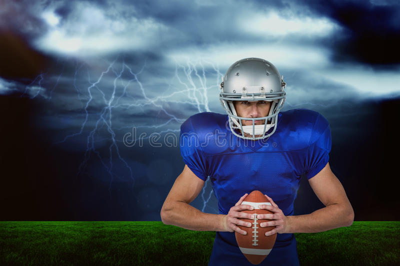 Composite image of confident american football player holding ball stock image