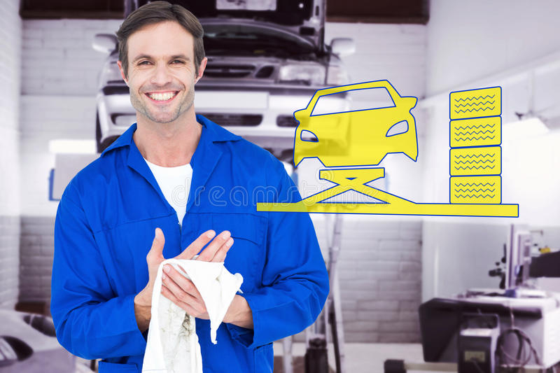 Composite image of confident mechanic wiping hand with napkin stock photography