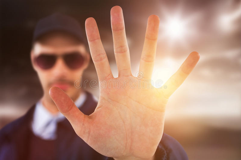 Composite image of confident security officer making stop gesture royalty free stock photography