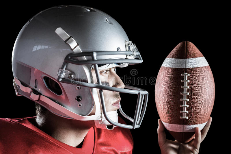 Composite image of confident sportsman looking away while holding ball royalty free stock image