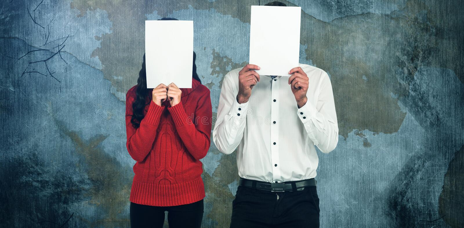 Composite image of couple hiding face with papers royalty free stock photos