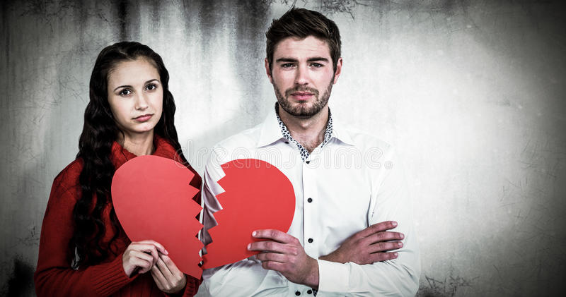 Composite image of couple holding heart halves royalty free stock image