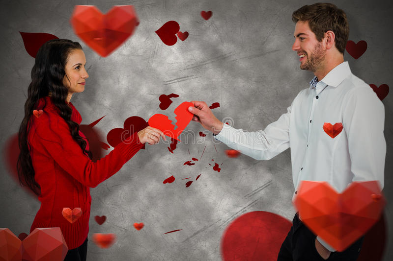 Composite image of couple holding red cracked heart shape. Couple holding red cracked heart shape against love heart pattern stock photo