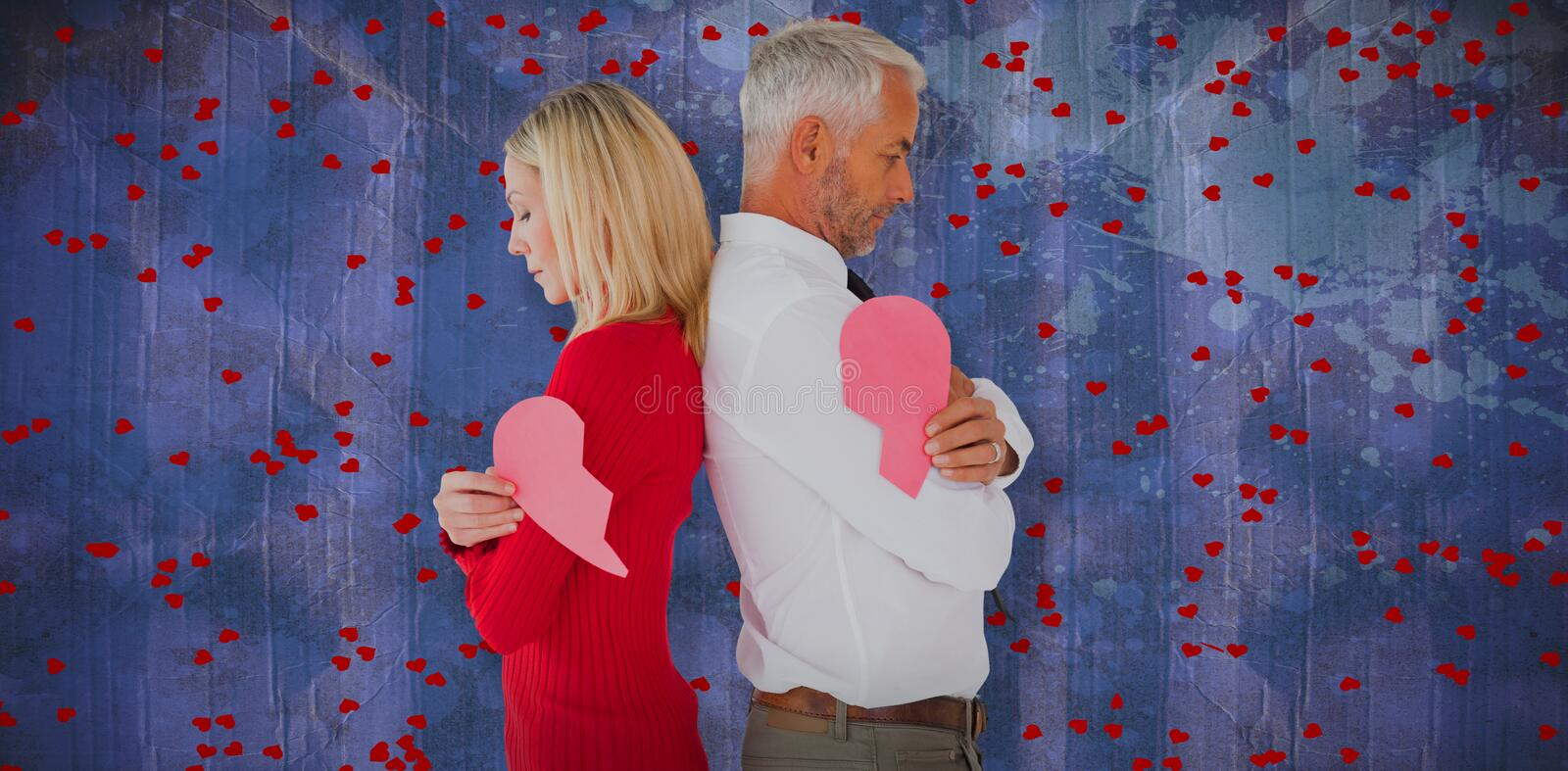 Composite image of couple holding two halves of broken heart. Couple holding two halves of broken heart against blue paint splashed surface royalty free stock photos