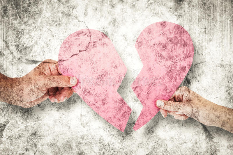 Composite image of couple holding two halves of broken heart. Couple holding two halves of broken heart against grey background royalty free stock image