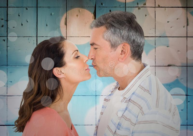 Composite image of couple kissing against blue tiles with bokeh. Composite image of mature couple kissing against blue tiles with bokeh royalty free stock photos