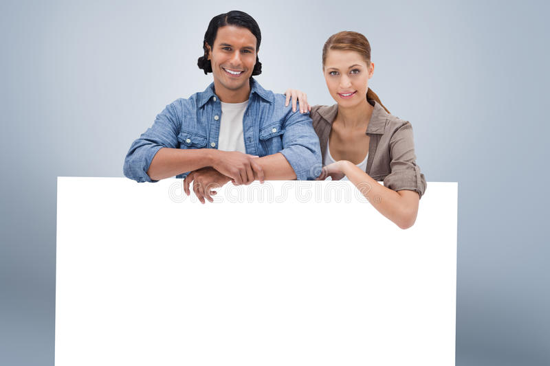 Composite image of couple leaning on blank wall. Couple leaning on blank wall against grey vignette royalty free stock photography