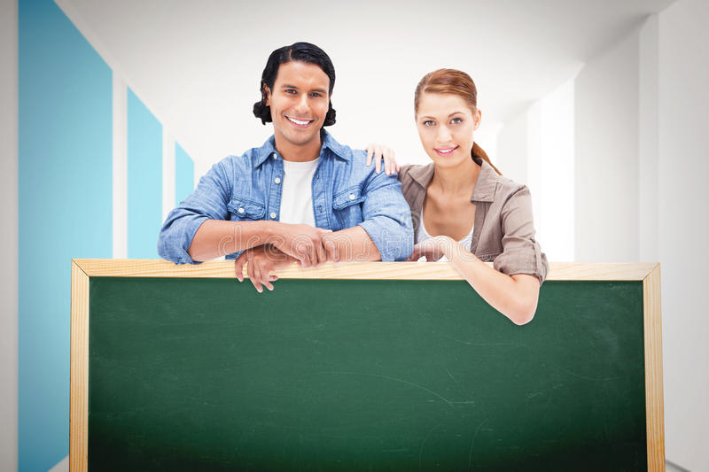 Composite image of couple leaning on blank wall. Couple leaning on blank wall against modern blue and white room royalty free stock photos