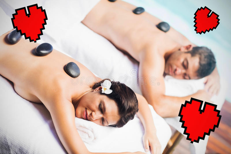 Composite image of couple in spa and hearts. Heart against couple getting hot stone massage stock images