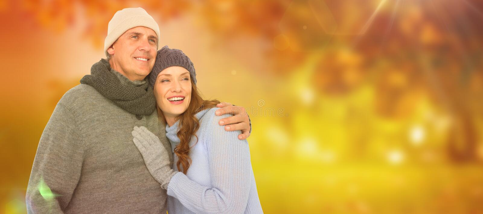 Composite image of couple in warm clothing embracing. Couple in warm clothing embracing against autumn scene stock photos