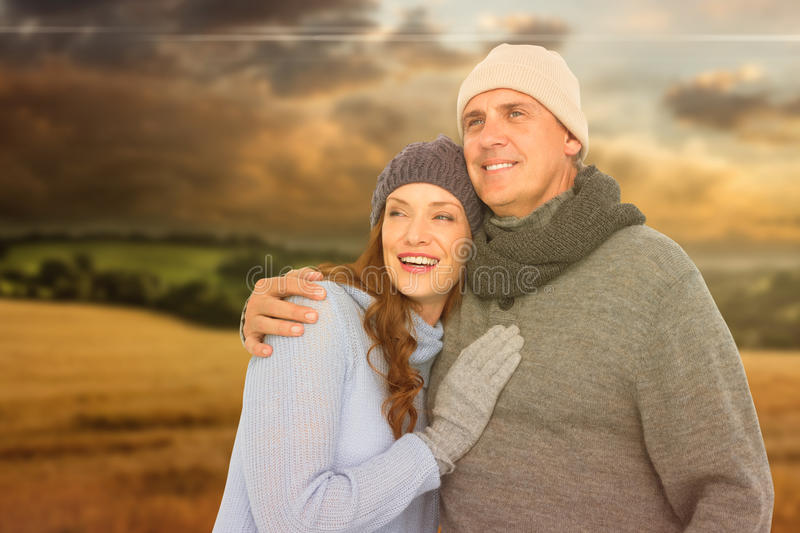Composite image of couple in warm clothing embracing. Couple in warm clothing embracing against country scene stock image