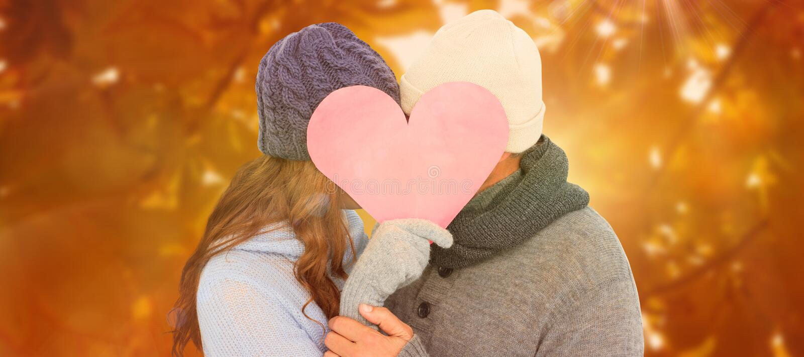 Composite image of couple in warm clothing holding heart. Couple in warm clothing holding heart against autumn scene royalty free stock images