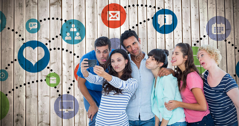 Composite image of creative business team taking a selfie. Creative business team taking a selfie against wooden planks background royalty free stock photos