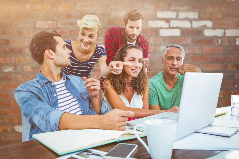 Composite image of creative business team using laptop in meeting. Creative business team using laptop in meeting against brick wall royalty free stock photography