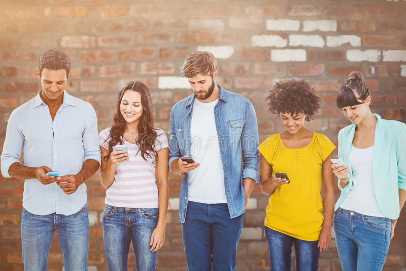Composite image of creative colleagues with mobile. Creative colleagues with mobile against brick wall royalty free stock images
