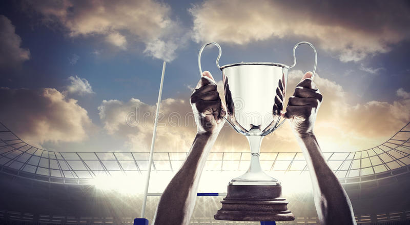 Composite image of cropped hand of athlete holding trophy royalty free stock photo