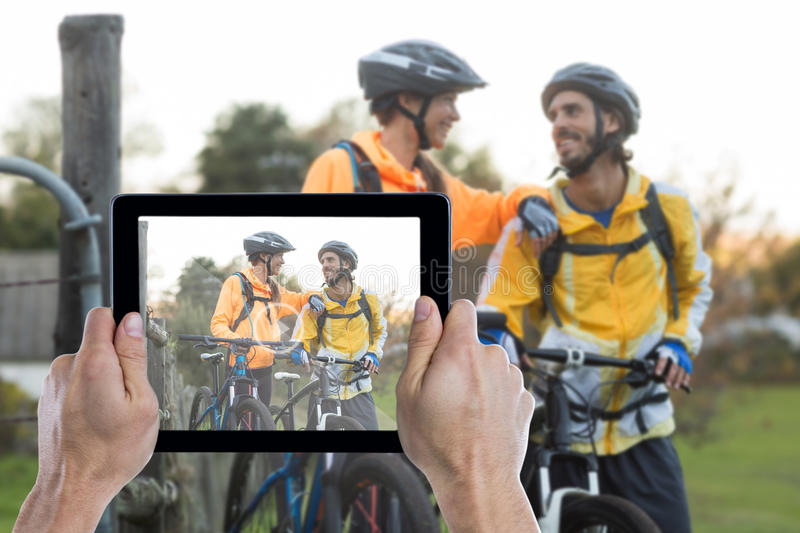 Composite image of cropped hand holding digital tablet. Cropped hand holding digital tablet against biker couple interacting while standing with mountain bike stock photo