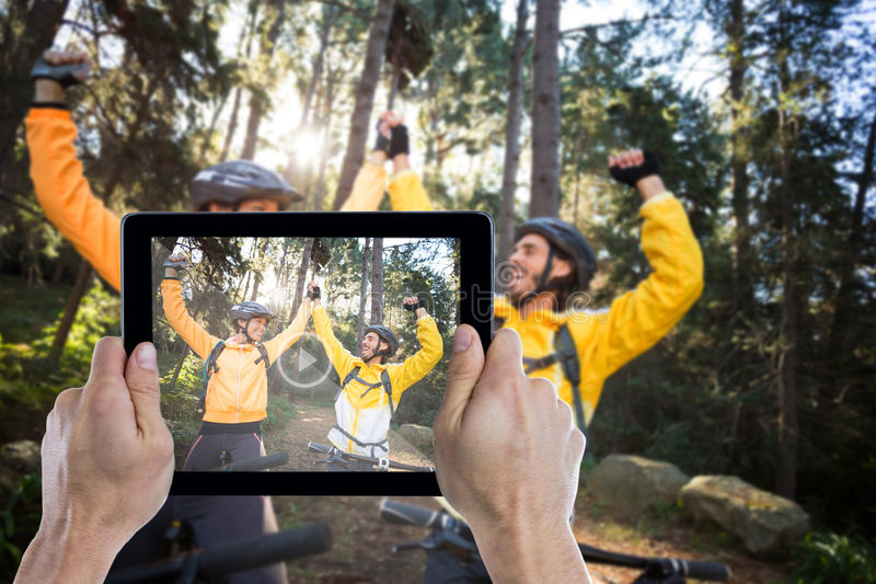 Composite image of cropped hand holding digital tablet. Cropped hand holding digital tablet against biker couple with mountain bike in countryside royalty free stock image