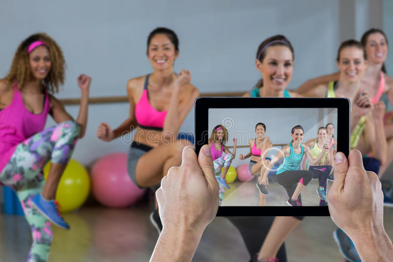 Composite image of cropped hand holding digital tablet. Cropped hand holding digital tablet against group of women performing aerobics stock photography