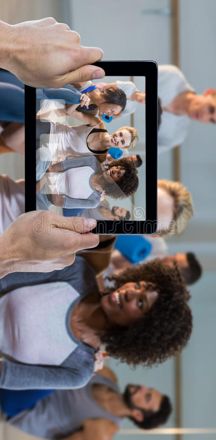 Composite image of cropped hand holding digital tablet. Cropped hand holding digital tablet against women sitting on floor royalty free stock image