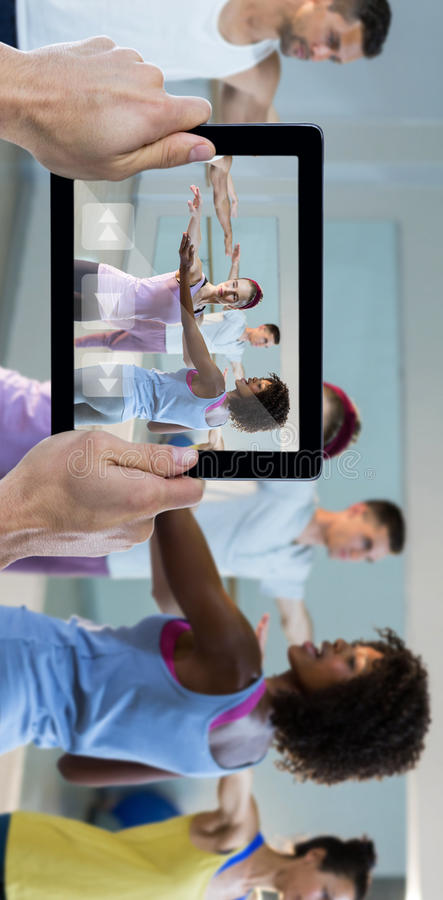 Composite image of cropped hand holding digital tablet. Cropped hand holding digital tablet against yoga instructor helping student with correct pose stock photography