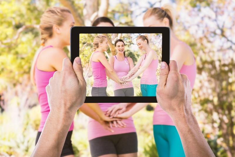 Composite image of cropped hand holding digital tablet. Cropped hand holding digital tablet against female volunteers stacking hands royalty free stock photography