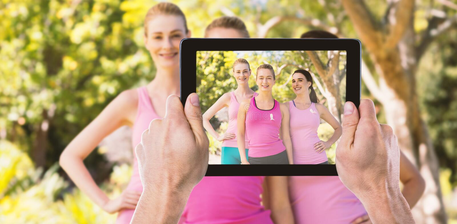 Composite image of cropped hand holding digital tablet. Cropped hand holding digital tablet against portrait of happy volunteers supporting breast cancer royalty free stock images