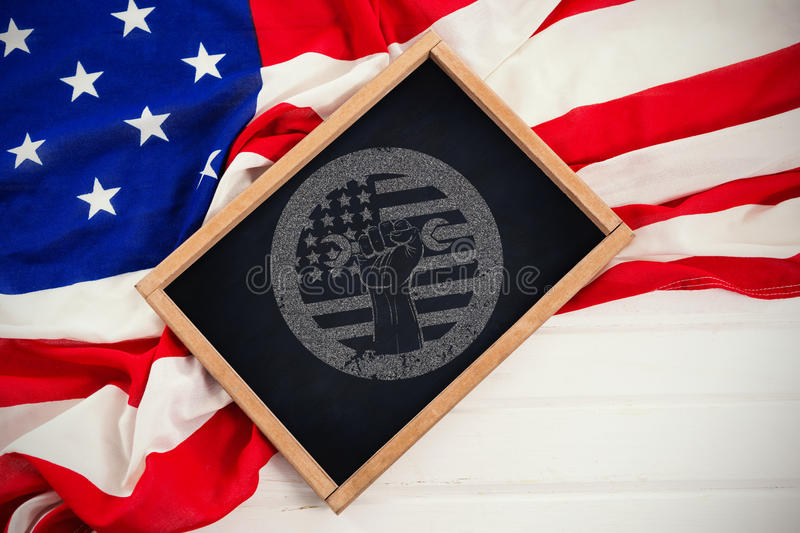 Composite image of cropped hand holding tool and american flag on red poster royalty free stock image