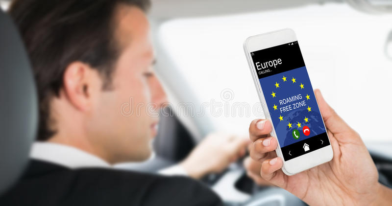 Composite image of cropped image of businesswoman holding smart phone. Cropped image of businesswoman holding smart phone against businessman in the drivers seat royalty free stock photo