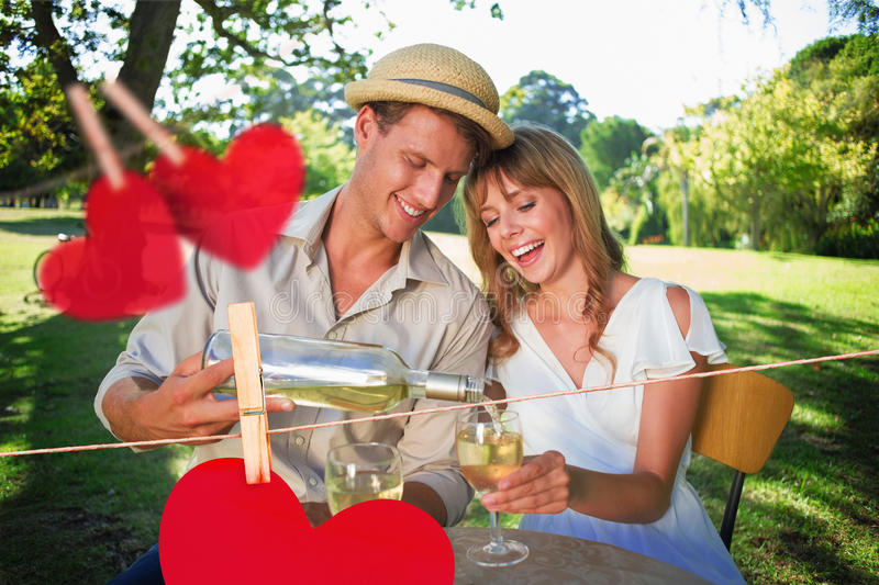 Composite image of cute couple drinking white wine together outside. Cute couple drinking white wine together outside against hearts hanging on a line royalty free illustration