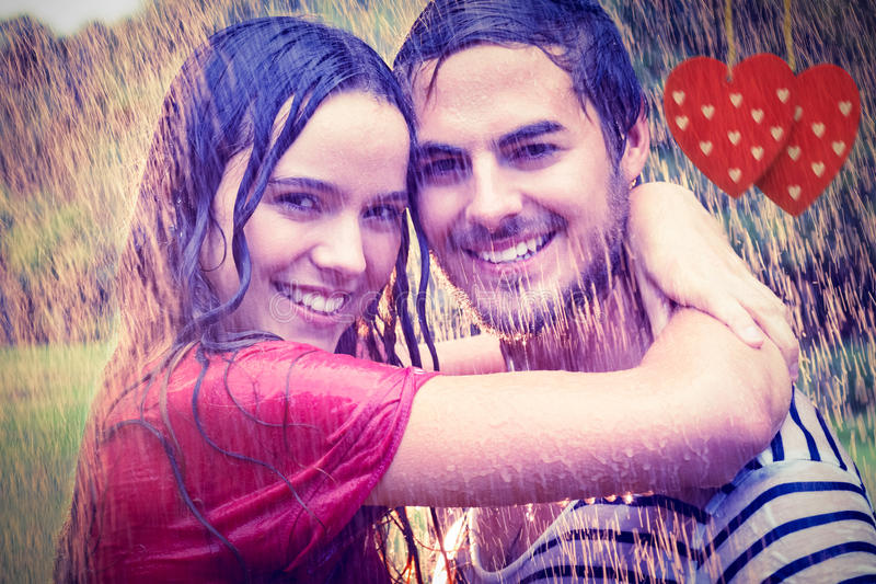 Composite image of cute couple hugging under the rain. Cute couple hugging under the rain against hearts hanging on a line stock photography